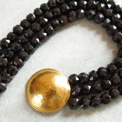 """Das Collier aus der Kollektion """"Schnecken"""" besteht aus Granat-Edelsteinen und einer geschmiedeten, vergoldeten Schnecke als Verschluss."""