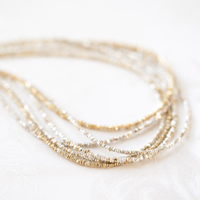 """Aus der Kollektion """"Klassisch, klar, kunterbunt"""": Ketten, die aus kleinen, eckigen Gold- und Silberplättchen bestehen."""