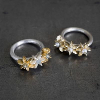 """Aus der Kollektion """"Gold- und Silberblümchen"""" geschmiedete Ringe mit Sterlingsilber-Blümchen, feinvergoldet, und Perlen."""