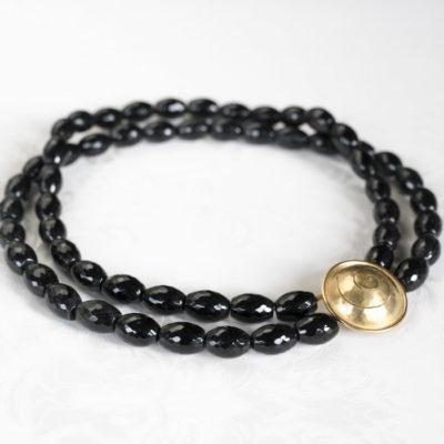 """Das Collier aus der Kollektion """"Schnecken"""" besteht aus Onyx-Edelsteinen und einer geschmiedeten, vergoldeten Schnecke als Verschluss."""