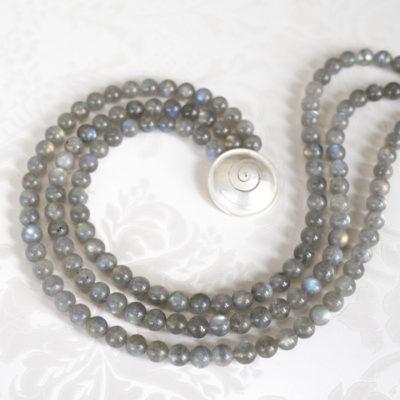 """Das dreireihige Collier aus der Kollektion """"Schnecken"""" besteht aus Labradorit-Edelsteinen und einer geschmiedeten, vergoldeten Schnecke als Verschluss."""