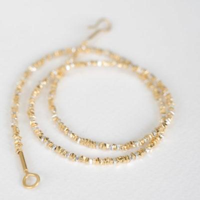 """Aus der Kollektion """"Klassisch, klar, kunterbunt"""": Kette, die aus kleinen, eckigen Gold- und Silberplättchen besteht."""