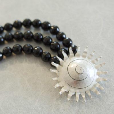 """Das Collier aus der Kollektion """"Schnecken"""" besteht aus Edelsteinen und einer aus Sterlingsilber geschmiedeten Schnecke als Verschluss."""