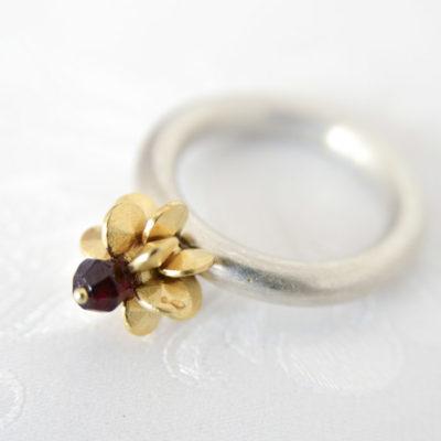 """Aus der Kollektion """"Gold- und Silberblümchen"""" geschmiedeter Ring mit Sterlingsilber-Blümchen, feinvergoldet, Granat.."""