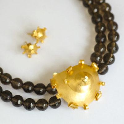 """Das Collier aus der Kollektion """"Schnecken"""" besteht aus Rauchquarz-Edelsteinen und einer geschmiedeten, vergoldeten Schnecke als Verschluss. Dazu passende Ohrstecker."""