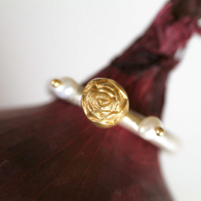"""Der Ring aus Christine Rettingers Kollektion """"Röschen"""" ist handgefertigt und wird geschmückt von Blümchen aus feinvergoldetem Sterlingsilber, begleitet von zwei Perlen."""