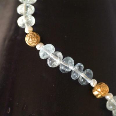 """Die Kette aus Christine Rettingers Kollektion """"Röschen"""" besteht aus Aquamarinen und Perlen, ergänzt von kleinen Röschen aus feinvergoldetem Sterlingsilber."""